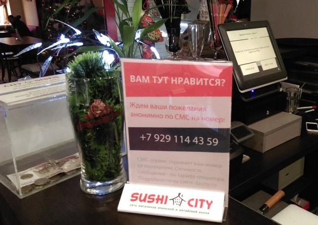 Табличка с номером телефона службы отзывов DASMS в кафе Sushi City