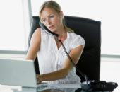 Сотрудница в офисе говорит по телефону