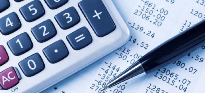 Калькулятор и ручка на фоне документа с расчётом