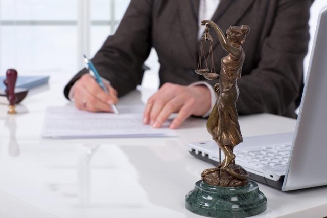 Мужчина за столом, пишущий что-то на листке бумаги