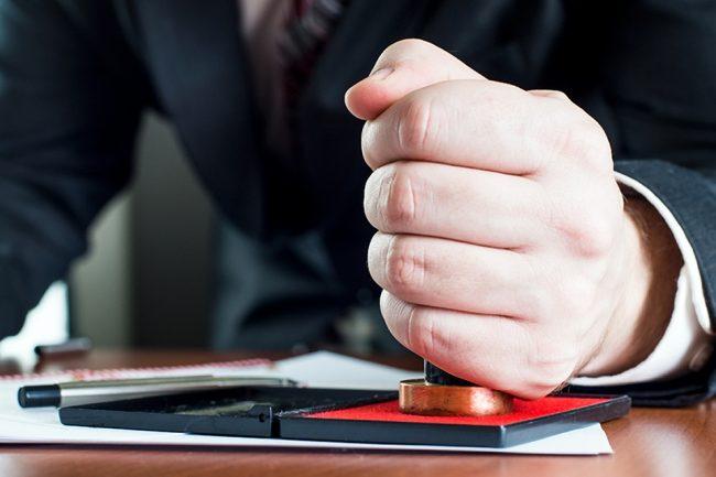 Мужской кулак, в котором зажата печать