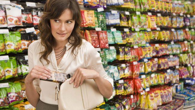 Девушка в магазине прячет шоколад в сумку