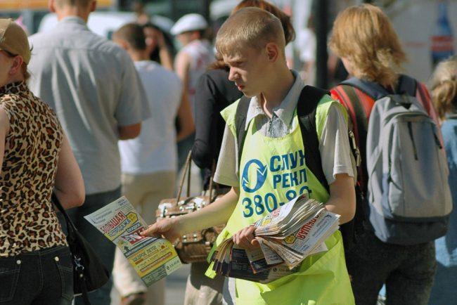 школьник раздаёт газеты