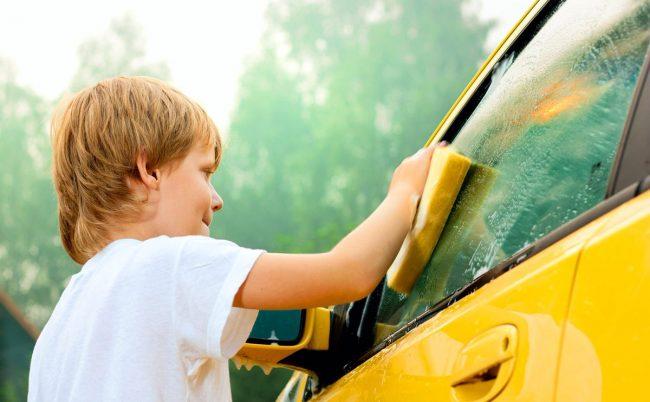 мальчик моет окно машины