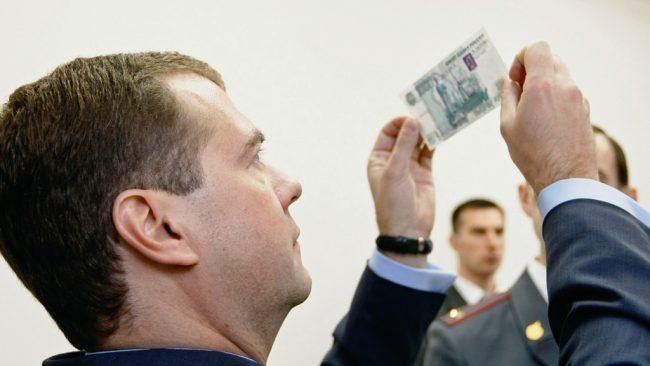 Дмитрий Медведев просвечивает тысячную купюру