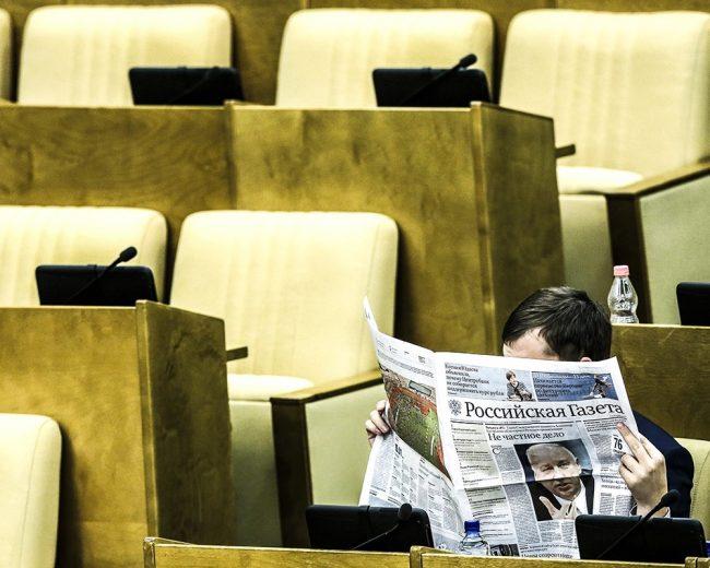 Депутат читает газету в Госдуме