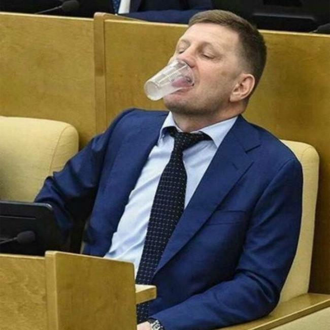 Депутат в Госдуме держит стакан ртом