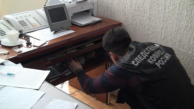 Сотрудник следственного комитета проводит обыск стола