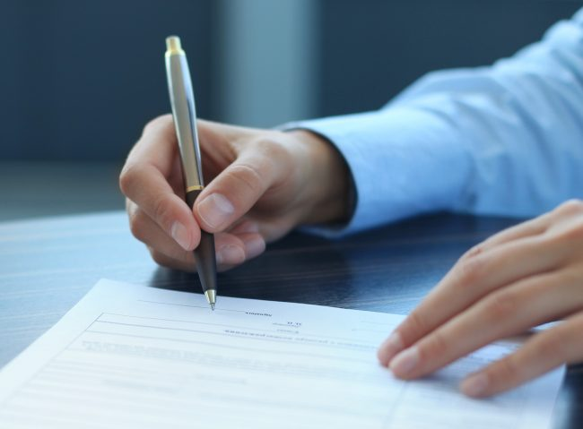 Человек ставит подпись